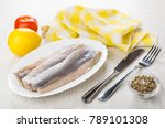 Stock photo fillet of herring in dish napkin lemon tomato condiment knife and fork on wooden table 789101308