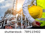 Small photo of Double exposure Engineers holding safety helmet in arms and holding walk talky in hands with oil and gas refinery background on industry concept
