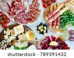 Small photo of Table full of mediterranean appetizers, tapas or antipasto. Assorted Italian food set. Delicious snack on party or picnic time. Chopping board with meat and cheese. Italian style banquet. Top view.