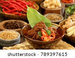 Small photo of Rendang Padang. Spicy beef stew from Padang, Indonesia. The dish is arranged among the spices and herbs used in the recipe.