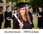 Small photo of Happy cute brunette caucasian grad girl is smiling, blurred class mates are behind. She is in a black mortar board, with red tassel, in gown, with nice brown curly hair, diploma in hand