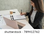 Small photo of Businesswoman at work signing a contract paper in her workstation