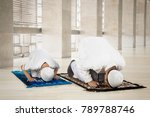 Small photo of Image of Muslim man with his son posing prostration while praying in the mosque