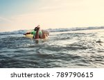 Small photo of Boy floats on surf board. Beginner surfer, first lessons
