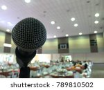 Small photo of selective focus of microphone on a deejay and emcee stage on a wedding ceremony in big hall.