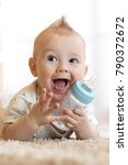 sweet baby boy holding bottle... | Shutterstock . vector #790372672