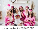 Small photo of Portrait of beautiful young bridesmaids in pink robes and sleep masks holding cupcakes with berries. Attractive bride in white robe with berry cake.