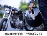 Handsome man in jean is holding a helmet and vintage motorcycle blur background