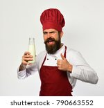 Small photo of Chef with milkshake or yoghurt shows thumbs up. Man with beard holds bottle of milk on white background. Organic ingredients concept. Cook with flirty face in burgundy uniform has liter of fresh milk