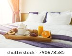 Stock photo breakfast served in bed on wooden tray with tea juice cookies and fruit hotel room service 790678585
