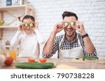 Small photo of Father is coocking with daughter. Father's Day concept. A little girl and dad have fun in the kitchen. Cucumber instead of eyes.