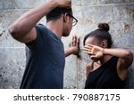 Small photo of Violent young man threatening his girlfriend with his fist outdoors