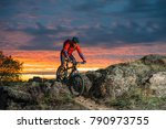 Cyclist in Red Riding the Bike on the Autumn Rocky Trail at Sunset. Extreme Sport and Enduro Biking Concept. - stock photo