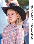 Small photo of Williams Lake, British Columbia/Canada - July 2, 2017: a young girl in a cowboy hat watches the Stampede Parade, a popular annual event in downtown Williams Lake.