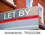 Small photo of LET BY sign displayed on London street with traditional English terraced houses in the background