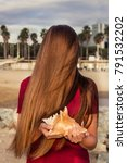 Small photo of A girl with long red hair in a red dress holding a big shell