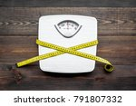 Stock photo lose weight concept scale and measuring tape on dark wooden background top view 791807332