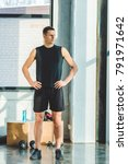 Small photo of young sportsman akimbo in sportswear standing in gym