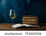 Small photo of Glass with White Wine, Books Connected by a Juggle Rope, An Open Book and Pen.