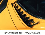 Small photo of Luxury yellow vintage roadster fragment, aerodynamics air intake grille on a car bonnet