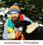 Small photo of Macho with beard hugs dog and holds cup. Man wears knitted hat, scarf and gloves with black dog. Guy with smiling face with firtrees covered with snow on background. Friendship and allegiance concept.