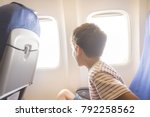 young boy on a airplane looking ... | Shutterstock . vector #792258562
