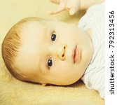 Small photo of Cute baby boy blond infant with blue eyes in romper lies on his back on beige bed cover