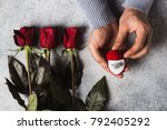 Small photo of Valentines day romantic man hand holding engagement ring in box marry me wedding with red roses bouquet gift surprise on grey background. Love gift for woman making proposal