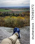 Small photo of Feet Dangle Over a Mountain Overlooking a Farm Field in the Fall Season