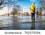 lady standing in flooded street ... | Shutterstock . vector #792575296
