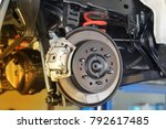 Disc brake of the vehicle for repair, in process of new tire replacement. Car brake repairing in garage.Close up. - stock photo