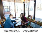 Small photo of Lawyer meet with client at cafe to discuss divorce process, young man and woman wearing formal clothes sitting near table with menu and communicating. Male suggest girl to make order, lady refuse