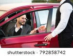 Small photo of Valet Giving Receipt To Young Male Businessperson Sitting Inside Red Car