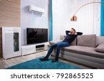 Young Man Relaxing On Sofa Nea...