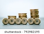 Small photo of EBITDA letter blocks and stacked coins. EBITDA stands for Earnings Before Interest, Taxes, Depreciation and Amortization.