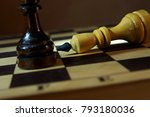 Small photo of Chess king loses to adversary. Defeat and Victory. Concept with wooden chess pieces
