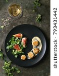 Small photo of Fried scallops with lemon, figs, sauce and green salad served on black plate with glass of white wine over old dark metal background. Top view, space. Plating, fine dining