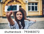 Half length portrait of positive female blogger traveller in stylish hat smiling at camera while shooting video of herself and showplaces on smartphone camera during weekend trip in architectural city - stock photo