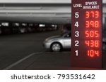 Small photo of Indoor parking garage sign. Red lighted numbers showing available spaces on each level. Shallow depth of field. Blurred background.