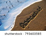 Small photo of Remember handwritten on sandy beach with soft ocean blue wave on background