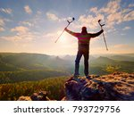 Small photo of Hiker with medicine crutch above head achieved personal target. Broken leg fixed in immobilizer Deep misty valley bellow silhouette of man with hand in air. Spring daybreak