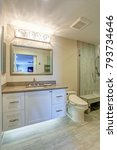 Small photo of Contemporary bathroom design boasts white vanity cabinet with taupe Quartz countertop, silver beaded mirror, decorative Lighting.