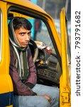 Small photo of KOLKATA, INDIA - JANUARY 10, 2018: A driver sitting in an Indian yellow taxi Hindustan Motors Ambassador model