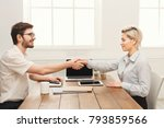 Small photo of Young casual business partners work in modern office. Shake hands as a sign of a good deal