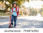 Young Boy Riding Scooter Along...