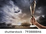 man's hand is holding gold cup... | Shutterstock . vector #793888846