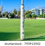 Small photo of One Australian football goal post wrapped with protective padding in a football oval at Arden Street Oval, Melbourne, Australia