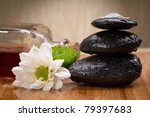 black balanced stones, flower and essential oil bottle - stock photo