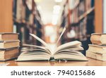 Small photo of Education learning concept with opening book or textbook in old library, stack piles of literature text academic archive on reading desk and aisle of bookshelves in school study class room background