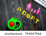Small photo of Adopt word, paper silhouette of family and toys near keyboard on